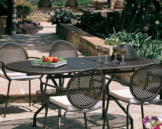 Metal Oval Outdoor Extension Dining Table - Metal, oval shaped outdoor extension dining table has a mesh metal top and a hole for an umbrella.