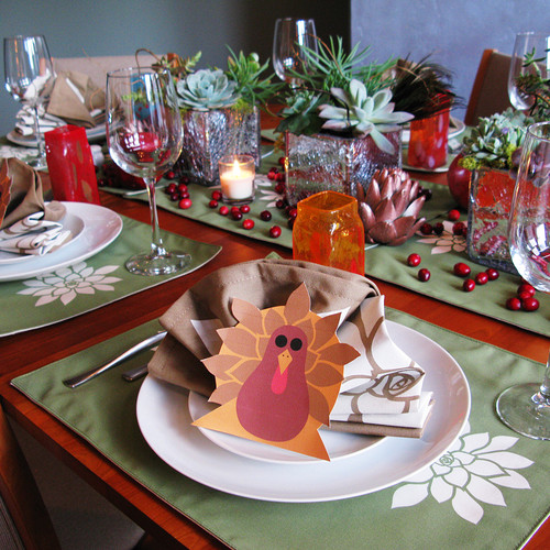 Thanksgiving table with crafted turkey place cards, white plates, and acorn and plant centerpiece