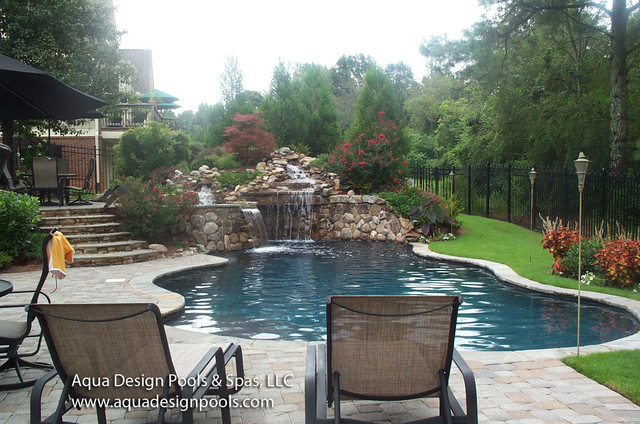 A craftsman pool with spa and waterfall features for Pool design by laly llc