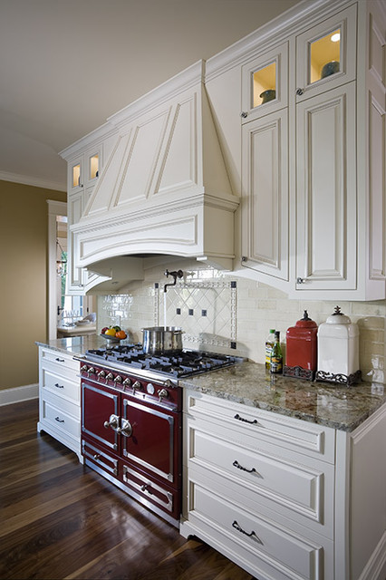 Red range with wood vent hood. traditional-kitchen