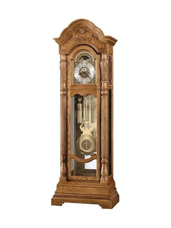 Howard Miller - Howard Miller - Nicolette Floor Clock - Time tarries in this voluminous, golden oak grandfather floor clock featuring hypnotic brass accents, cast corner and center ornaments, a silver chapter ring with applied brass Arabic numerals and exquisite craft detailing to captivate your home's d̩cor. * This stately floor clock offers a graceful bonnet pediment with book-matched olive ash burl and a decorative shell and vine overlay. . An astrological blue moon phase draws attention to the polished brass dial, which features cast corner and center ornaments, a silver chapter ring with applied brass Arabic numerals, and an Ambassador Collection inscription. . The polished brass pendulum includes a center disk which complements the dial and coordinates with the banded, polished brass weight shells. . The reeded columns are capped with elaborate carvings that frame the dial. . An embossed molding wraps around the multi-tiered base, which features a decorative cutout. . Crystal-cut and grooved glass enhances the front lower door, with beveled glass on the lower side panels. . Removable, fret-cut, top side panels allow easy access to the movement. . A Howard Miller Heirloom capsule with a certificate is included for documenting the clock history for future generations. . Cable-driven, triple chime Kieninger movement offers automatic nighttime chime shut-off option. . Finished in Golden Oak on select hardwoods and veneers. . Adjustable levelers under each corner provide stability on uneven and carpeted floors. . The case is illuminated by an interior light. . You will receive a free heirloom plate, engraved with name and date, by returning the enclosed request card to Howard Miller. . Locking door for added security. . Glass mirrored back beautifully showcases your collectibles.. Manufacturer's 2 Year Warranty . 90 1/4 in. (229 cm) H x 30 1/2 in. (77 cm) W x 17 3/4 in. (45 cm) D