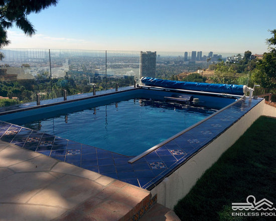 Original Endless Pools® - What makes this Endless Pool® installation stand out? The bold blue tile coping. The unobtrusive see-through protective barrier. The sprawling view of downtown Los Angeles.