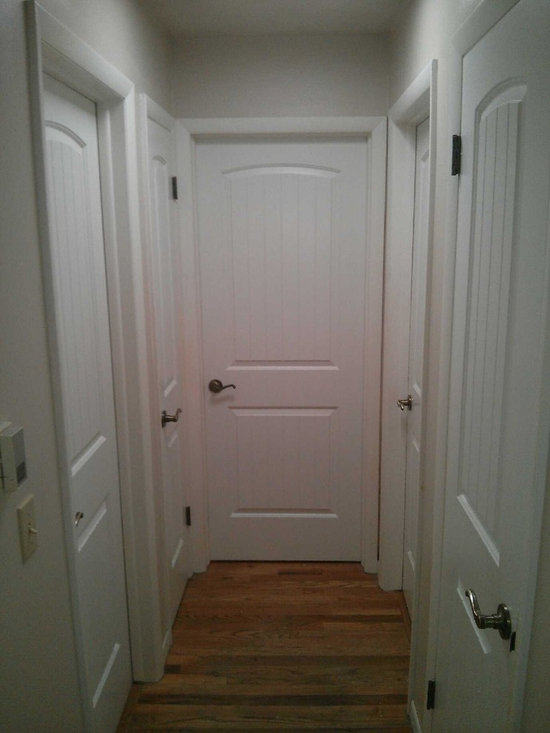 Complete Interior Door Replacement - New bright white Santa Fe style door with brush nickel knobs. Totally transforms the hallway  and accentuates  the natural wood floor.