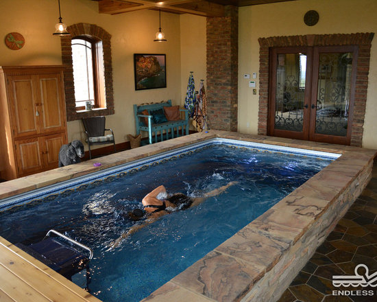 Original Indoor Endless Pool® - Arched windows, brick accents, and rich ochre walls bring a bit of Tuscany to this pool room. The modular Endless Pool, here finished with marble tile and multicolored stone, can be easily assembled in existing spaces.