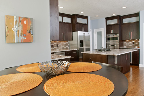 a modern brown kitchen with captivating orange placemats