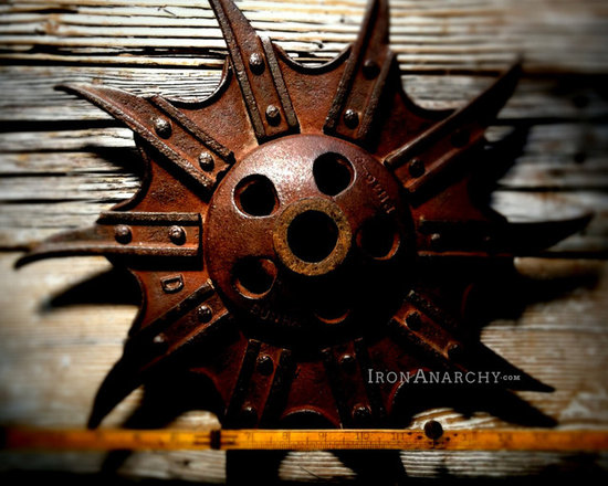 """Antique Industrial Gear Decor - Ultra-amazing old wheel in a """"stop-dead-in-your-tracks"""" design in extra-thick, exta-chunky iron! Curved spikes riveted to a webbed, bat-wing-like wheel. 17"""" diameter."""