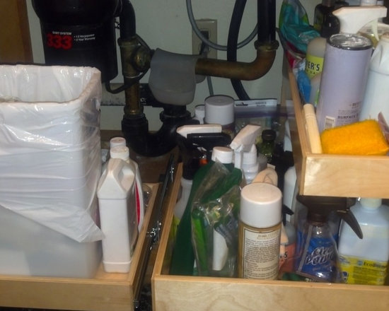 Kitchen Pull Out Shelves and Pull Out Trash Bin - This cabinet features a pull out trash bin on the left, and a pull out shelf with a riser shelf on the right.  As you can see, there is a lot of plumbing in this sink.  All ShelfGenie of Los Angeles pull out shelves and accessories are custom made so we can work around these types of obstacles without compromising storage space.