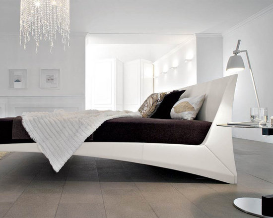 Dylan Designer Leather Bed By Cattelan Italia - Beautiful and well crafted its unique curve and elevated design gives you a bed that appears cantilever in design giving your bedroom a contemporary look that`s outstanding. The bed is in fact supported by 4 legs like any other normal bed but the beauty of this design is the positioning of these legs which makes it seem like a Floating Bed (Click on the additional pictures below to main picture to view the legs)The design of the Dylan Contemporary Bed pays the greatest attention to padding upholstery and the kind of leather used making it a state-of-the art product.