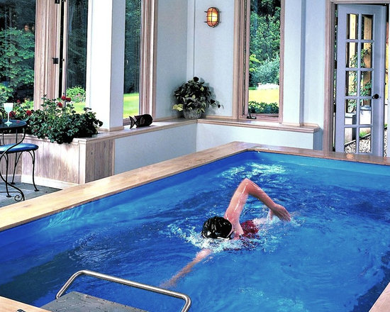 Indoor Endless Pool® - Light blues and pale woods make the most of this sunroom's natural light. It's a placid environment for all-season swimming in the compact Endless Pool. With its modular construction, the Pool easily installs in existing indoor spaces.