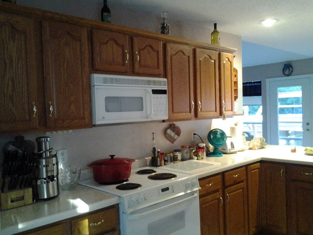 have honey oak cabinets and a light mauve formica countertop with
