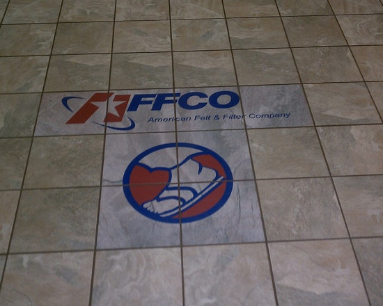 Custom Floor Tile designs and ideas - Custom printed floor tile. Ceramic floor tile was given slightly different background marbling color to contrast with field tile. Logo from brochure was enlarged and improved with graphics software and then digitally printed on the ceramic floor tile. By custom-tiles.com