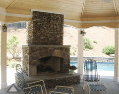 Open porch with stacked stone fireplace from Atlanta Decking and Fence Company