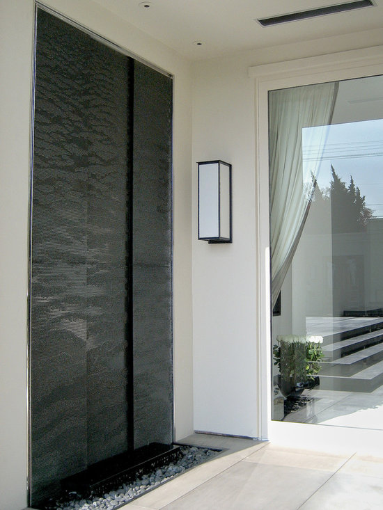Beverly Hills Residence - Recessed water wall, composed of three panels, approximately 5 ft. wide by 12 ft. tall, was custom designed for a residential space in Beverly Hills, California.  The water wall is composed of ridged, absolute black granite and surrounded by a stainless steel frame.  Beneath the water wall lies a small reflection pool and a bed of black river rocks.