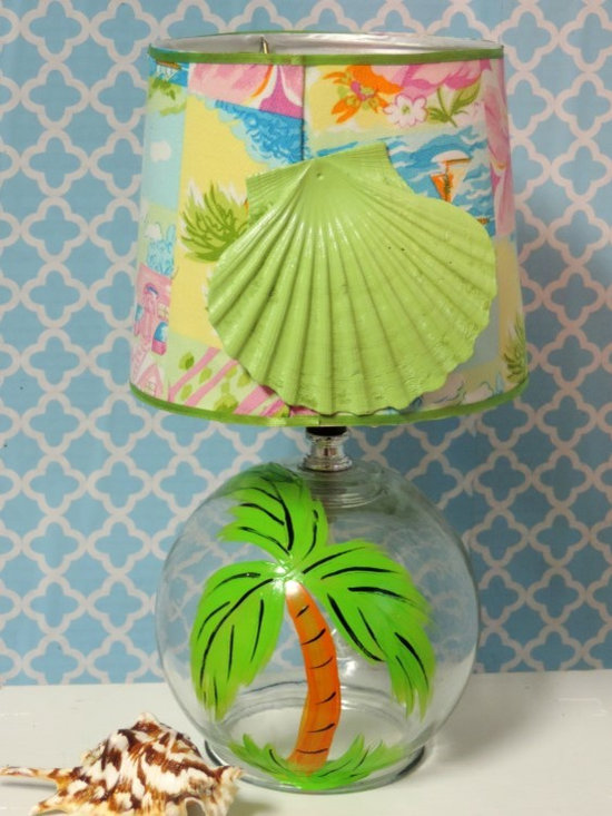 Seaside Living: A Hand Painted Palm Tree Lamp - Perfect for a beach inspired home, this glass lamp features a hand painted palm tree. The shade has been wrapped in a vibrant beach fabric and embellished in a lime green clam shell for added fun. This one of a kind lamp would be a delightful addition to a cheerful seaside retreat.