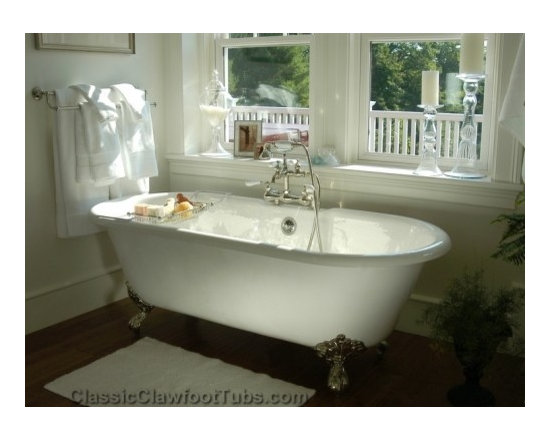 Gorgeous bathroom with a double ended clawfoot tub - A drop dead gorgeous bathroom featuring a cast iron double ended clawfoot tub positioned in front of window.  Once of our favorite pictures of a traditional bathroom overlooking a deck on the second floor.