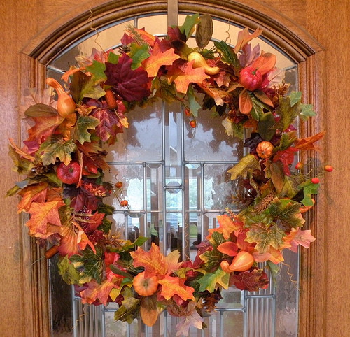 a lovely autumn wreath featuring leaves, pumpkins and berries