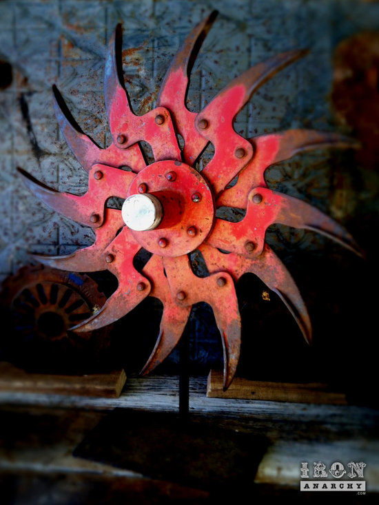 """Antique Industrial Gear Decor - Extra-amazing old metal wheel with a very nasty disposition! Angry, zig-zag claws of 1/4"""" thick steel bound together with bulging round head rivets. Worn, aged patina with remnants of red paint to ensure you know it means business! Mounted on a custom aged metal stand. 17"""" diameter, standing 21"""" tall overall."""