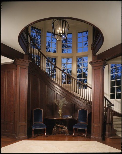 A circular, wooden, closed-stringer staircase with a runner carpet.