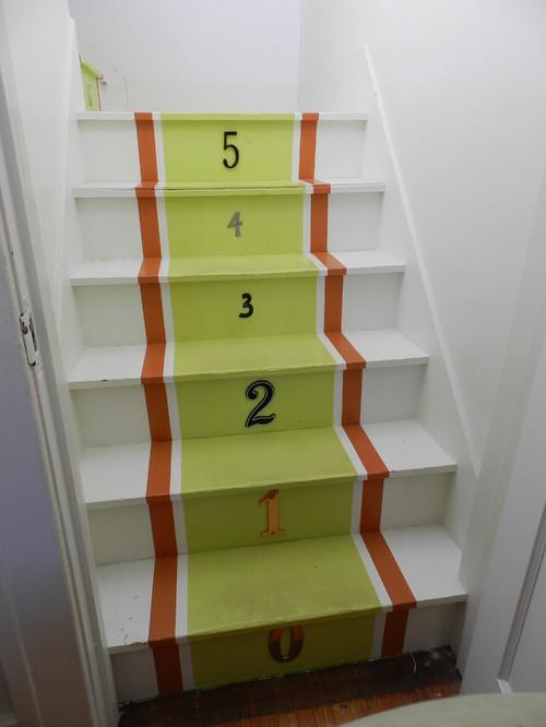 Escaleras pintadas en blanco verde y naranja y con números en cada escalon