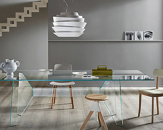 Modern Living - Table with extra clear glass surface resting on a luxurious wing structure. The central beam of varying length is held by two extremely optimized legs inspired by the '50s and the formal and structural experimentation of Jean Prouvé.