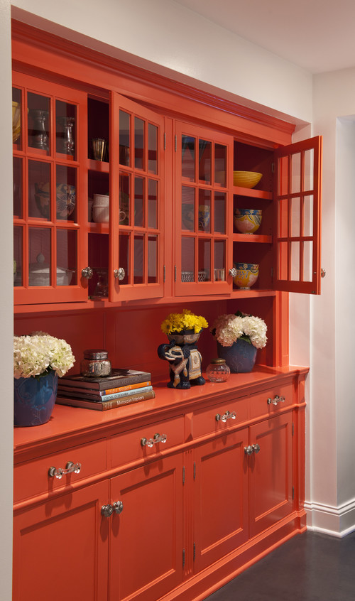 Bright orange built-in dining room hutch cabinets with glass doors.