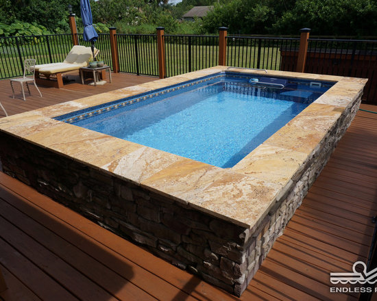 Original Endless Pools® - The broad marble border and ragged brick siding provide the yang to pool's deep-blue yin. Even with its compact, eco-friendly design, the Endless Pool can be customized to make a powerful statement, redefining this otherwise simple deck/lawn arrangement.