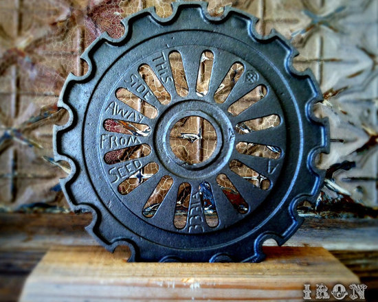 """Antique Industrial Gear Decor - Fantastic old gear in an ornate industrial design. Engraved hand-written text to make it even more intriguing! Although from the 1920s, this cast iron wheel has had its thick rusty surface scoured away to reveal a sparkling bright gun metal finish. Reclaimed lumber display stand. 7 5/8"""" diameter."""