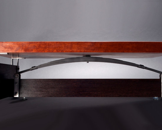Bubinga Table with Knots - This table created from a knotty bubinga solid hardwood slab, is supported by a clever repurposing of a sports car leaf spring, combined with wenge hardwood. Stewart Tilger Photography