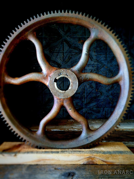 Antique Industrial Gear Decor - Very rare mid-1800s gear of cast iron with curved spokes and an engraved numeral indicating the number of teeth along its wide rim. Sits in a rustic reclaimed lumber display stand.