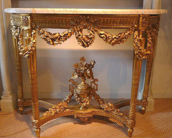 Fine, French, Louis XVI period, demi-lune console table - In solid, carved giltwood, having four, tapered, fluted legs joined by a stretcher centered with floral urn, the apron elegantly carved with bows and garlands, having a Carrera marble top.  From Paris circa 1780.