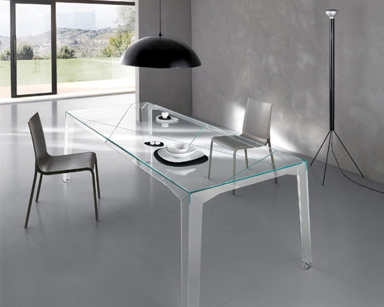 Fragments Table - Perfect couple between the possible, the product, and the impossible, the non-being designer. The lightness of the extra clear glass is opposed to the great stability granted by the slight outwards inclination of the legs. The incisions realized with craftmade mastery on the lower part of top and side give the illusion that the table is the result of an assembly of three-dimensional fragments. Available only in extra clear glass.
