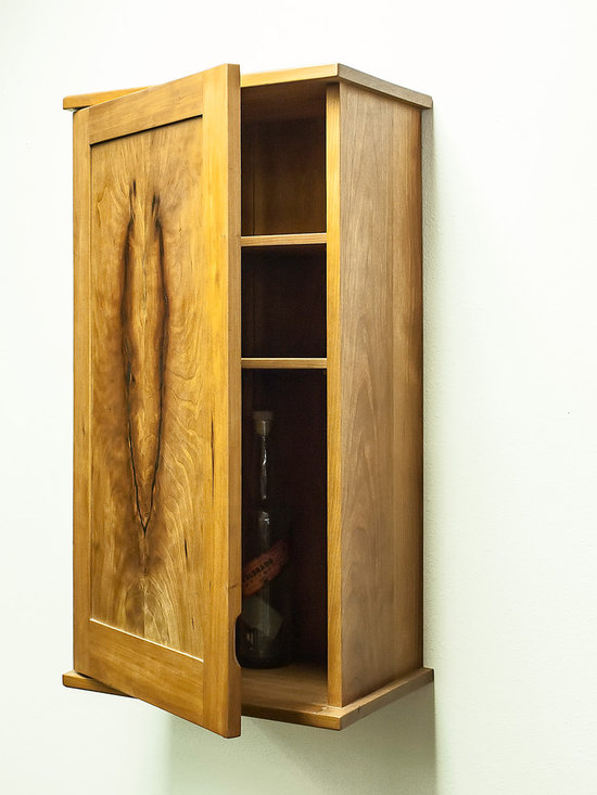 "Solid Cherry Krenovian Style Whiskey Cabinet - Handcrafted wall cabinet, perfect for your special whiskeys or brandies. The cabinet is 33 ¼"" high X 16 ¼"" wide X 10"" deep, constructed of prime American Cherry timbers matched on the sides and the door. The center panel is a book matched flame/crotch grained panel, unique to this piece. Some see the image of a deer skull in the panel. It has two adjustable interior shelves and a French cleat for an easy installation. Brass leaf hinges and shelf pins set off the cherry color. It is finished with French polish and wax."