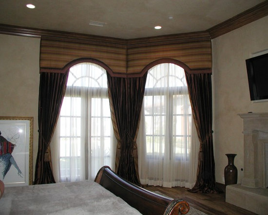 Top Treatments - Upholstered cornice boxes to match shape of windows with traversing sheer draperies and stationary side panels puddled at the floor beneath,