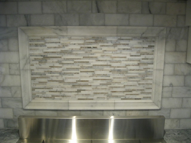 white marble backsplash with marble moulding frame inset with mixed