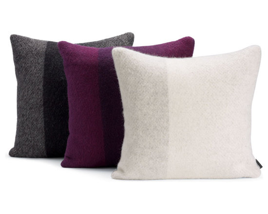 Berg Pillow | Designed by Torbjørn Anderssen and Es - Believing that color exerts a powerful influence on how we perceive the world around us, designers Anderssen and Voll celebrate their love of rich hues with the Berg Pillow (2010). These heavyweight wool pillows, with their simple aesthetic, are ombré dyed to create a shadowy stripe and tonal shift. They are made with lambswool by Røros Tweed, a leading producer of fine Norwegian products since 1939. The company is named for Røros, a copper mining town that that was transformed in 1789 when mine director Peder Hiort bequeathed his fortune to a foundation for the poor. The townspeople were taught how to spin, weave and sew warm clothing to survive the harsh winters, and in the process, the region became known for its rich tradition of handicraft and textile production. Røros Tweed also owes its success to the quality of its raw materials – free-roaming Røros sheep are truly pampered, grazing contentedly in fresh mountain pastures. Because the sheep are untroubled by insects in this cool climate, there is no need to use harsh chemicals to clean the wool. Røros Tweed's clients include the Japanese Emperor, Christian Dior and the White House. Small wonder, then, that the Berg Pillow received the Norwegian Design Council Award for Design Excellence. Made in Norway.