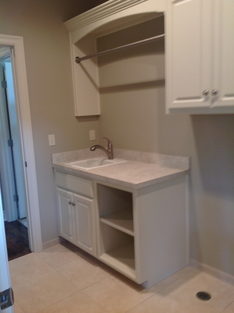 Laundry room like sink, cabinets and hanging rod