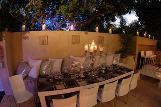 Outdoor dining room with elegant table setting and lots of candles.