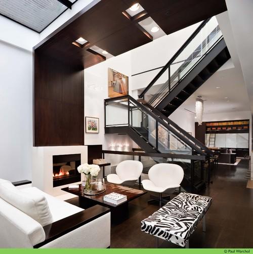 таунхаус гостиная с лестницей отделка панелями из дерева камин контрастные цвета белый черный темный