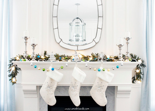 a clean mantel with a garland, silver candlesticks and christmas stockings